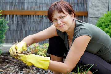 smiling middle age woman gardening in sunny day