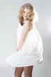 Young blonde girl posing in studio in white dress
