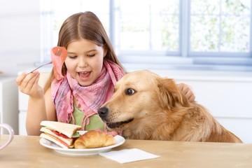 Little girl and dog having breakfast together