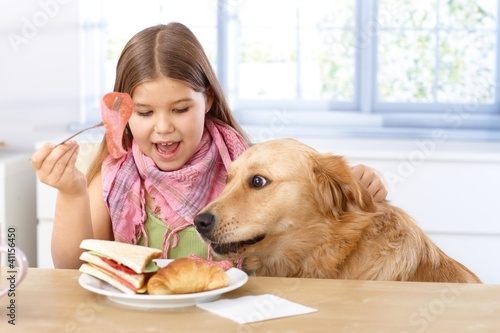 Little girl and dog having breakfast together