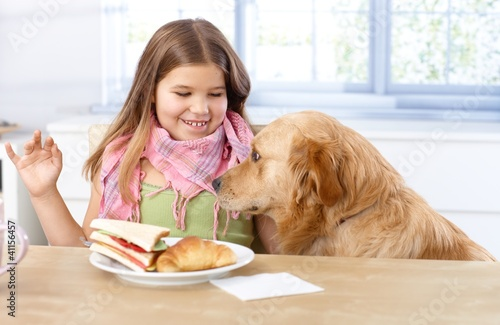 Little girl and dog at table having lunch smiling
