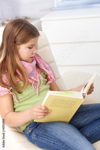 Little girls reading a book at home