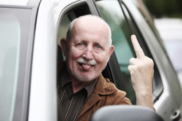 senior im auto zeigt stinkefinger