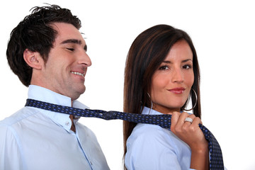 Woman leading a man by his tie
