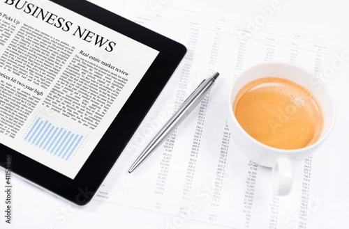Modern working place with business news on digital tablet