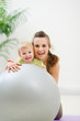 Portrait of smiling mother and baby behind fitness ball