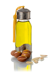 Glass bottle of argan oil with nuts and seeds