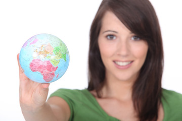 young woman holding out world globe