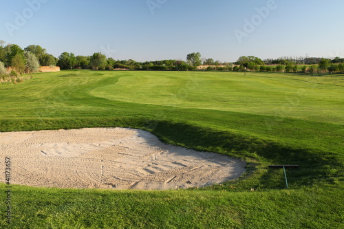 Sand bunker on the golf course with green grass