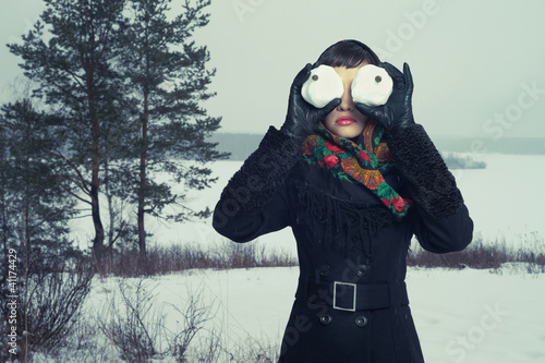 Humorous portrait of  woman with snow-balls