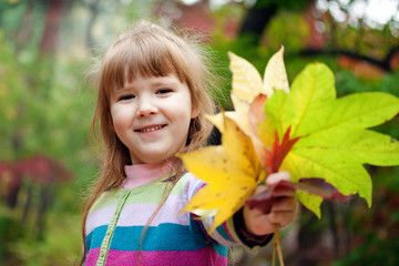 Cute smiling girl with fallen leaves
