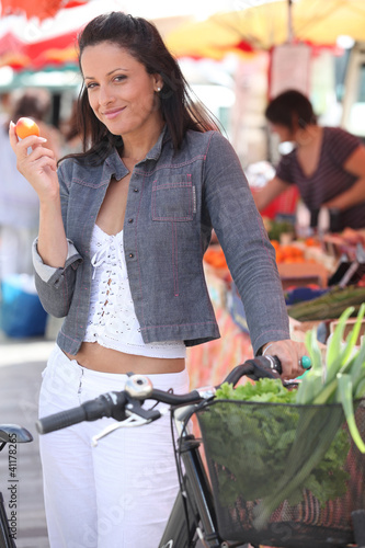 Woman eating a clementine at a market
