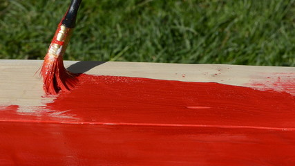 hand with brush paint in red a new wooden table boards