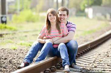 Couple sitting at railway.