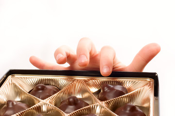 Child's hand picking chocolate candy from box isolated over whit