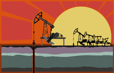 Oil pumping units against sunset.