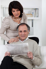 Man and woman reading newspaper