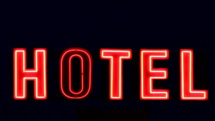 Señal de hotel con luces de neon por la noche