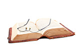 Old open bible with reading glases