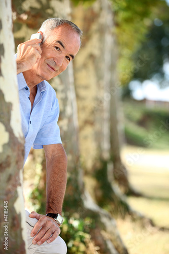 man with phone behind tree