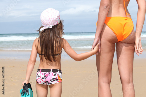 Mother and daughter holding hands on a sandy beach