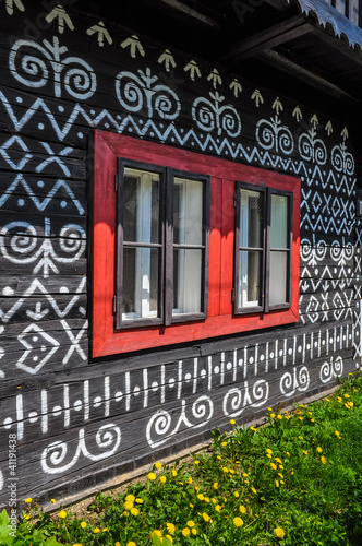 Colorful red windows on traditional wooden cottage - 41191438