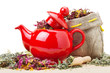 red teapot, mortar and pestle, sack with healing herbs