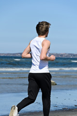 Athletic young male running on the beach. From the back.