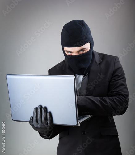 Computer Hacker in suit and tie stealing data from laptop comput