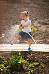 Cute Little girl watering flowers in the garden