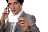 Man holding up his business card