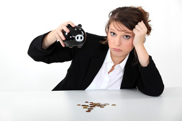 Woman emptying piggy bank