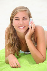 Blond teenager laying on a beach whilst making a call