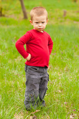 Cute angry little boy standing in the meadow on beautiful day