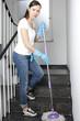 Frau reinigt das Treppenhaus