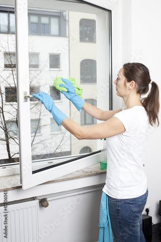 Frau putzt Fenster