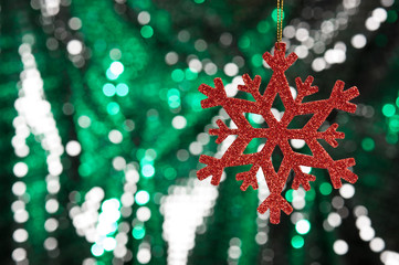 Red snow flake on a green, silver glitter background