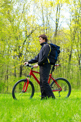 Man Cyclist with Bike and Backpack among the green nature