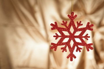 Red snow flake on a gold background