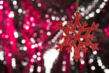 Red snow flake on a red, silver glitter background