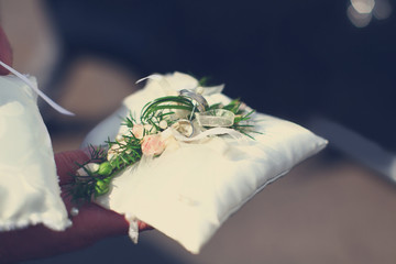 Golden rings on white pillow