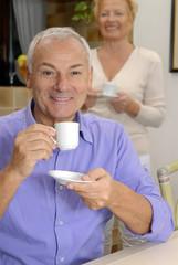 Pareja de señores bebiendo café en una cocina.