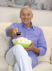 Un señor sentado en un sofá comiendo palomitas de maíz.