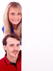 Junger Mann und junge Frau schauen lächelnd hinter Tafel hervor