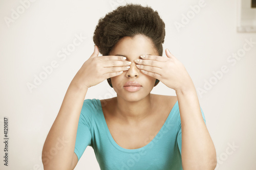Young woman closing eyes with hands