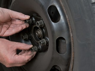 Close up photo of a mans hands changing a wheel