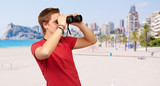portrait of young man looking through a binoculars at beach