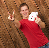 portrait of young man doing a victory gesture playing poker agai