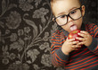 portrait of a handsome kid wearing glasses sucking a red apple a
