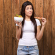 portrait of young woman choosing pizza or salad against a wooden